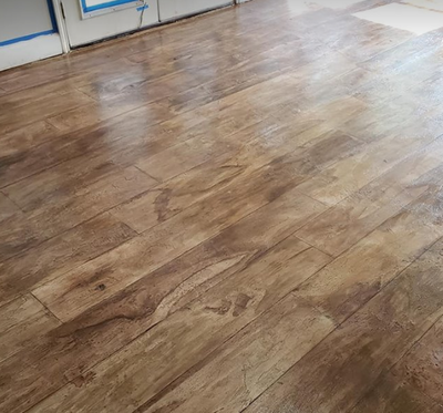 Concrete floor with brown wood color stain and hardwood stamp finish in Findlay hom