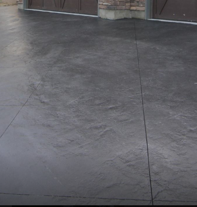 Natural rock textured stamp concrete with a dark gray color