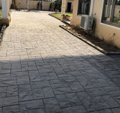 Stamped driveway with large brick paver design.